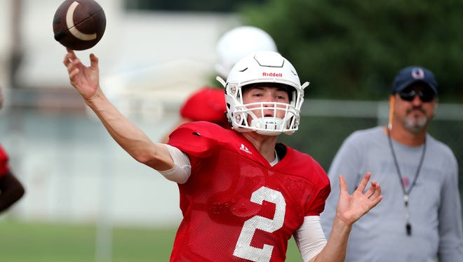 Oakland senior quarterback Brevin Linnell fires a pass as coach Kevin Creasy looks on during a recent practice. The Patriots will scrimmage McCallie, Cane Ridge and Brentwood Academy.