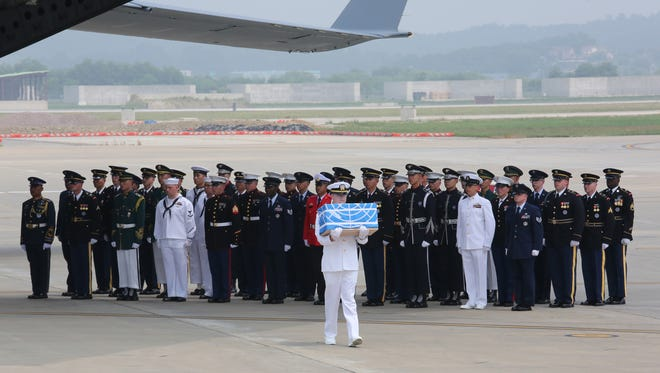 A U.N. honor guard carries a box containing remains believed to be from American servicemen killed during the 1950-53 Korean War after arrived from North Korea, at Osan Air Base.