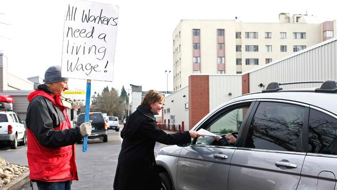 Maureen Crawford (center) hands a flier to a customer as Peter Bergel (left) looks on during a protest outside of the McDonald's restaurant on Center Street NE in December. Members of the OSEA are seeking an increase in minimum wage.