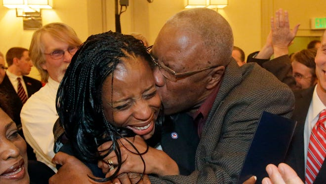 Republican Mia Love celebrates with her father, Jean Maxime Bourdeau, after winning the race for Utah's 4th Congressional District.