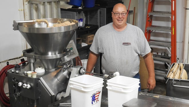 Dale Phillips stands in front of the machine used to process his natural casing hot dogs that will be shipped to Kroger.