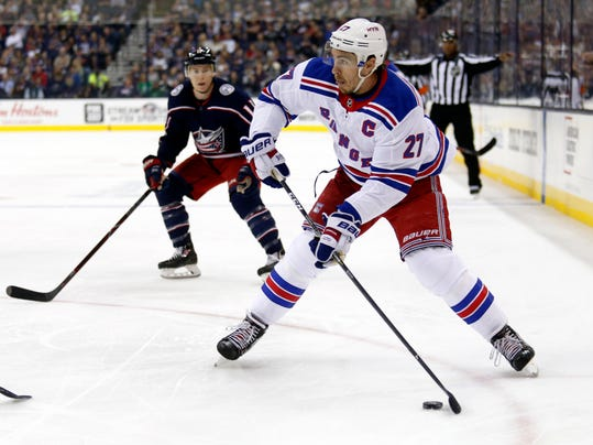 FILE - In this Oct. 13, 2017, file photo, New York Rangers defenseman Ryan McDonagh, right, looks to pass in front of Columbus Blue Jackets forward Matt Calvert during an NHL hockey game in Columbus, Ohio. The Tampa Bay Lightning have strengthened their NHL-leading team by acquiring Rangers' McDonagh. (AP Photo/Paul Vernon, File)