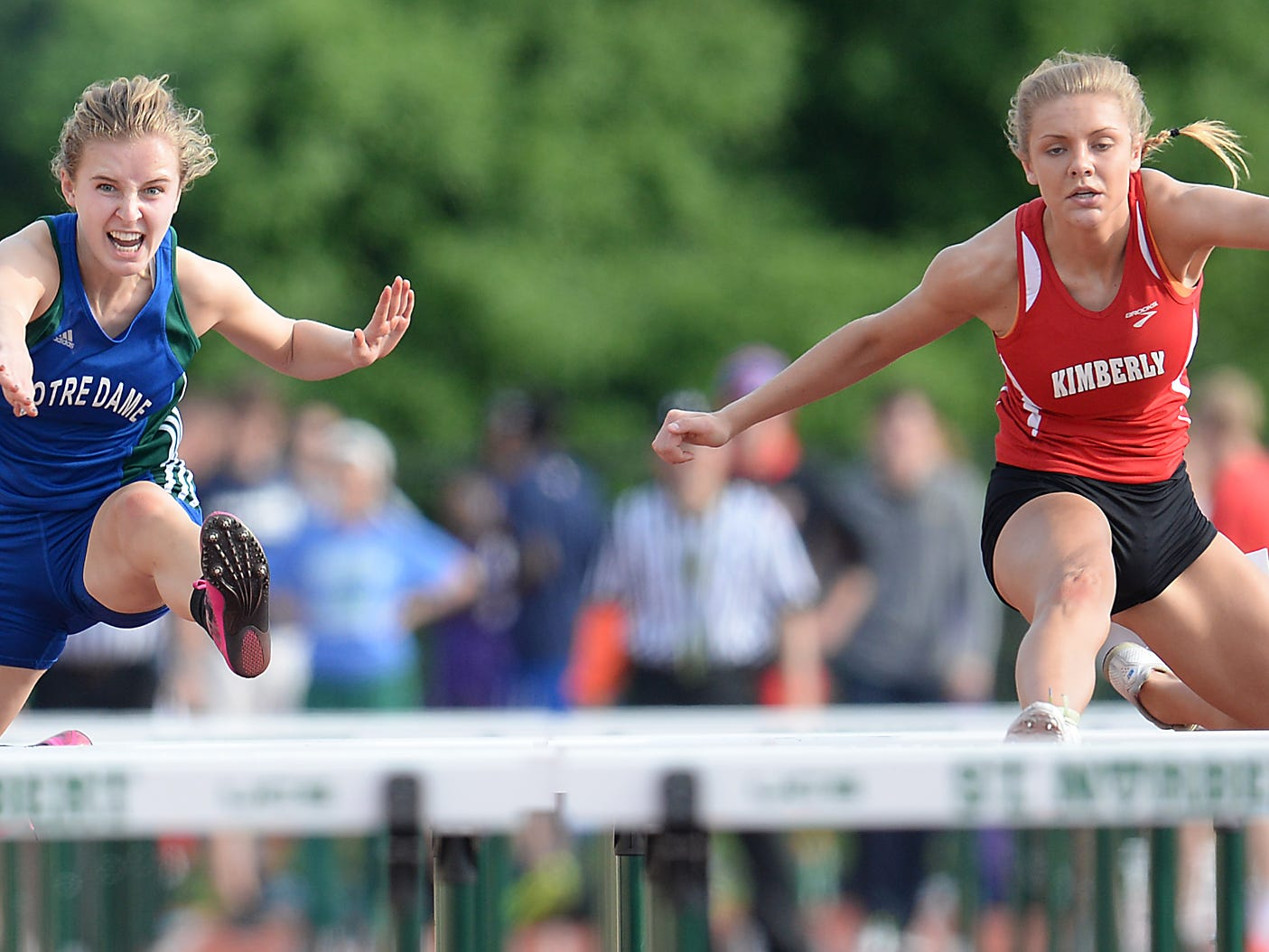 Kimberly's Kayla Vandehey (right) and Notre Dame's Liz Markland battle in the 100-meter hurdles Friday at Schneider Stadium in De Pere.