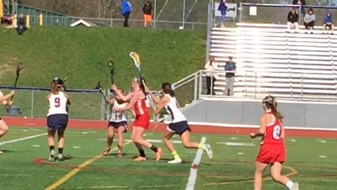 Owego's Abigail Higgins splits three Chenango Forks defenders en route to scoring in the first half of Monday's Section 4 Lacrosse Conference game at Forks.