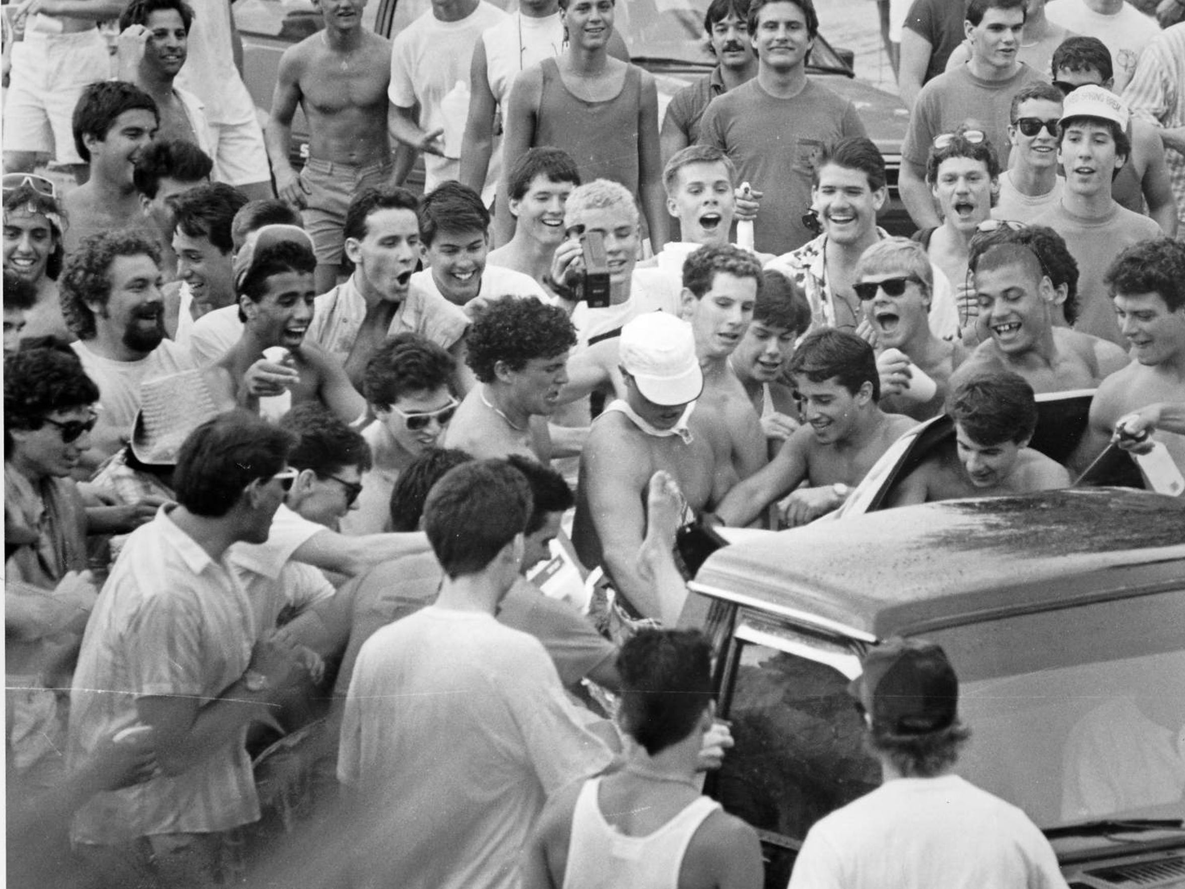 A mob of spring breakers attack a woman in the back of a pickup truck during the 1986 riot. Several women had their clothing torn off by the mob, and at least one woman reported to police she was sexually assaulted in the middle of the street.