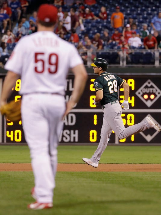 Oakland Athletics' Matt Olson, right, rounds the bases after hitting a two-run home run off Philadelphia Phillies starting pitcher Mark Leiter Jr. during the first inning of a baseball game, Friday, Sept. 15, 2017, in Philadelphia. (AP Photo/Matt Slocum)