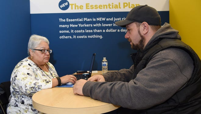 Bob Mihalchik of Wappingers Falls, right, speaks with New York State of Health insurance navigator Wanda Ramirez during an information drive at the Poughkeepsie Galleria on Saturday.