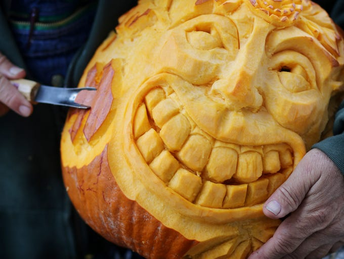 A face is carved into a pumpkin by a member of the