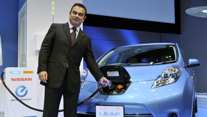 Nissan CEO Carlos Ghosn charges the electric vehicle Leaf. he says Nissan is on track with self-driving cars