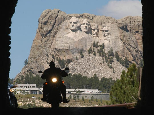 A biker rolls through a tunnel on Iron Mountain Road as Mount Rushmore stands in the background in 2004.