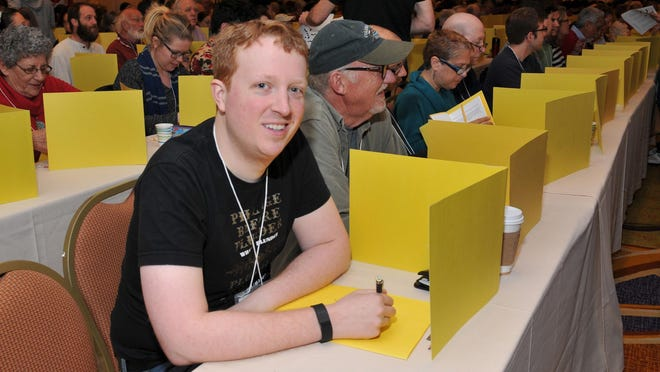 Tyler Hinman, who holds the record of the youngest to ever win the American Crossword Puzzle Tournament, sits among the puzzlers in the Stamford Marriott, in Stamford, Conn.