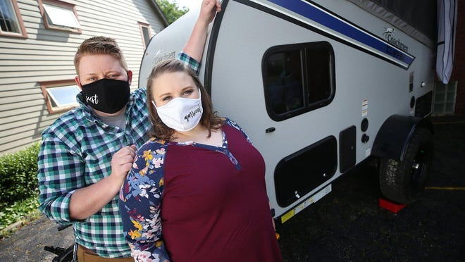 """Caroline Altizer, left, and her fiancee Natalie Miller pose in their masks that together say """"just married"""" in front of the camper they will be taking around the country to celebrate their June 20 marriage at the homes of their relatives."""