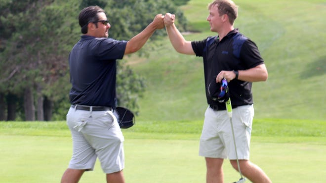 Runner-up Alek Dernalowicz, left, fist bumps winner Andrew Johnson after the final putts on the 18th green during Sunday's final round of the 84th annual Gardner Municipal Golf Course's Men's Club Championships. Johnson edged out Dernalowicz by two strokes to win his second club championship.