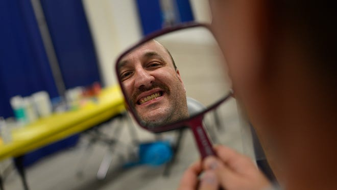 Mike Larsen of Oshkosh checks out his new smile after he was fitted for a partial Friday during the Wisconsin Dental Association's Mission of Mercy at the KI Convention Center in downtown Green Bay.