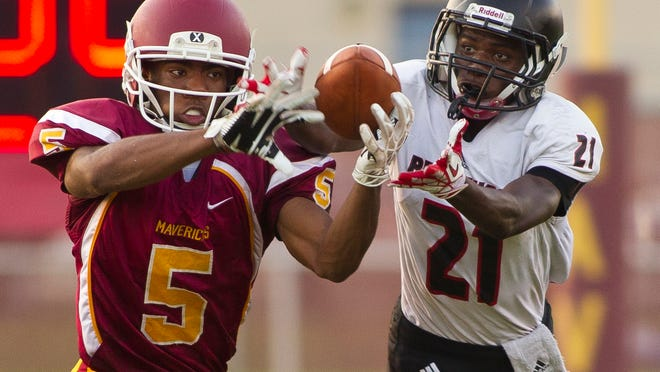 McCutcheon defensive back Tre'shon Heard and Lafayette Jeff receiver Desmond Wilson go for a pass that was eventually intercepted by McCutcheon's Cole Williams  during their game against Friday, September 5, 2014, at McCutcheon near Lafayette. The game was called because of lightning and will be resumed Saturday morning.