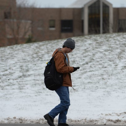 A student checks his phone while walking on campus
