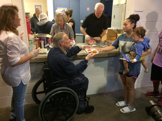 Greg Abbott helps serve dinner Saturday, Aug. 26, 2017, at a Red Cross shelter for hurricane evacuees in Austin. (Photo: John C. Moritz/USA Today Network ...