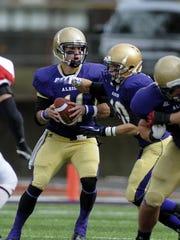 Albion College quarterback Dominic Bona (11) hands