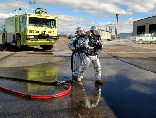 Airport emergency responders wet down a plane during