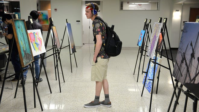 St. Cloud State University freshman Spencer Schrupp, 19, stops to look at the art show and benefit Wednesday at SCSU's Atwood Memorial Center. Money raised will go toward relief efforts in Nepal.