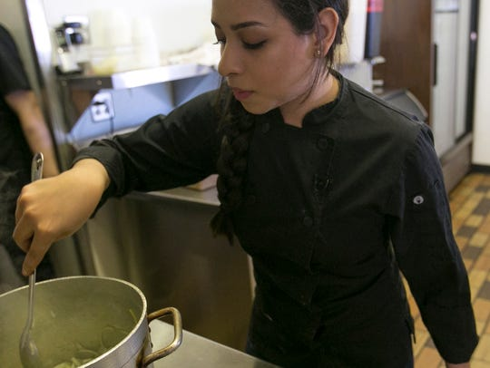 Nadia Holguin stirs cheese and onions in a pot at her