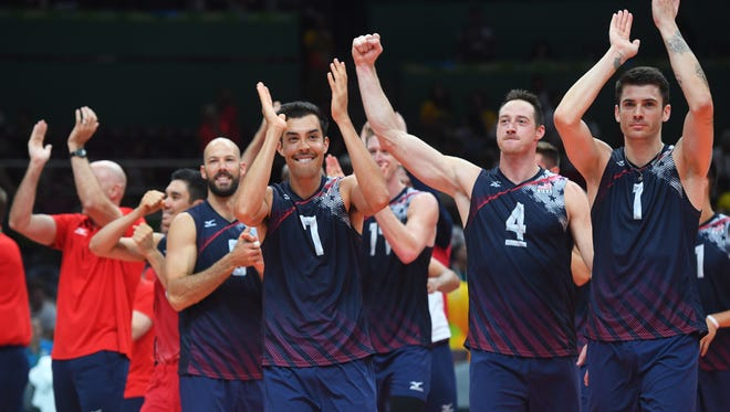 United States setter Kawika Shoji (7) and middle blocker David Lee (4) and opposite spiker Matthew Anderson (1) react after defeating Poland in a men's quarterfinal volleyball match at Maracanazinho during the Rio 2016 Summer Olympic Games.