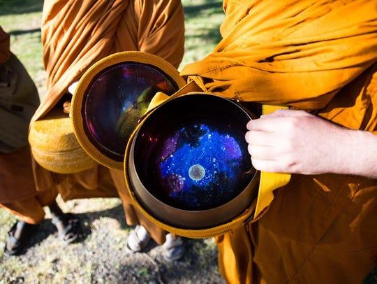 Ajahn Sudanto displays the inside of his alms bowl.