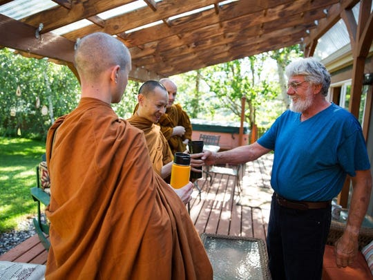 Ray Klebba, right, hands tea to Ajahn Kassapo on alms