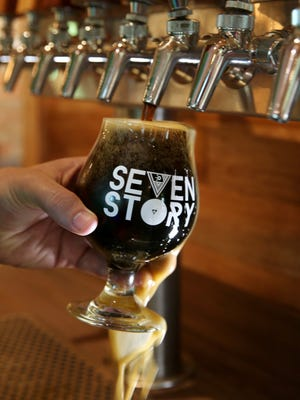Casey Dunlavey, co-owner, pours a pint of their porter beer at the new Seven Story Brewing in Perinton Wednesday, July 11, 2018.  The brewery is set to open in August.