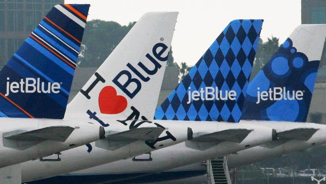 JetBlue planes, each with distinctive tail art, are seen at the JetBlue terminal at Long Beach Airport in Long Beach, Calif., on Oct. 25, 2011.