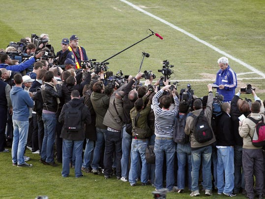 FILE - In this Sunday, June 20, 2010, file photo, France's soccer coach Raymond Domenech is surrounded by the media, while reading a letter from his players who decided to cancel the training session, in Knysna, South Africa. On this day: Four years on from losing the World Cup final to Italy in a penalty shootout, the French squad in South Africa for the 2010 tournament goes on strike. (AP Photo/Francois Mori, File)