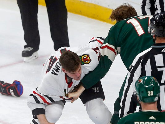 Chicago Blackhawks' Lance Bouma, left, and Minnesota Wild's Marcus Foligno fight during the first period of an NHL hockey game, Saturday, Feb. 10, 2018, in St. Paul, Minn. Both received fighting majors. (AP Photo/Jim Mone)