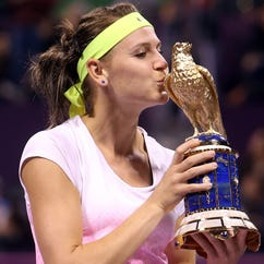 Lucie Safarova of the Czech Republic kisses the winner's trophy after her victory against Victoria Azarenka of Belarus during the final of the WTA Qatar Ladies Tennis Open in Doha, Qatar.
