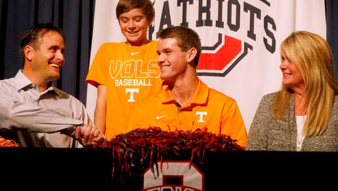 Oakland's Jacob Pennington shakes the hand of his father Paul Pennington as his bother Jeremy Pennington, 15, and mother Kim Pennington watch after Jacob Pennington signed to play baseball with the University of Tennessee Wednesday.