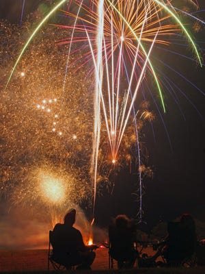 Area residents watch the fireworks display from the Alma Park upper area on Friday, July 3, 2020
