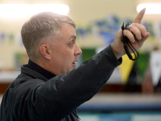 Swimming coach Ed McNamee gives signals to his swimmers during last year's crosstown swim meet at the Bill Swarthout Fieldhouse pool.