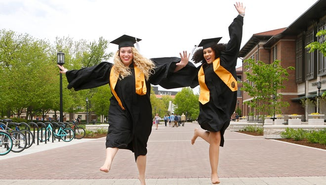 Constance Vendl, left, and Janel Scissom leap across Rush Crossing Friday, May 11, 2018, on the campus of Purdue University. Both women are English education majors and will graduate on Saturday.