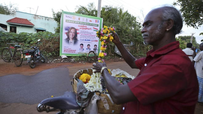 A local vendor sells flowers in front of a hoarding featuring U.S. Vice President-elect Kamala Harris in the hometown of Harris' maternal grandfather, in Thulasendrapuram, south of Chennai, Tamil Nadu state, India, Sunday, Nov. 8, 2020. After rooting for Kamala Harris as President-elect Joe Biden running mate, people in her small ancestral Indian village woke up Sunday morning to the news of her making history.