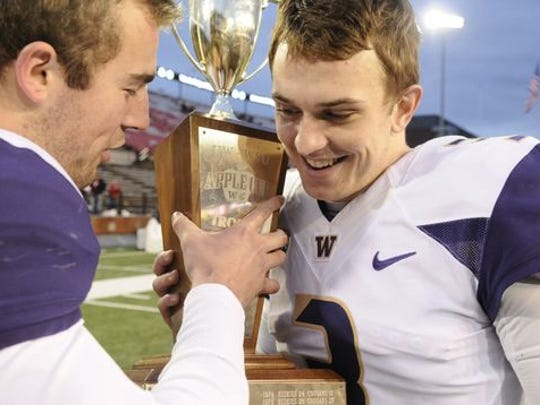 Washington Huskies quarterback Jake Browning (3) takes the the Apple Cup Trophy after a game against the Washington State Cougars after a game at Martin Stadium. The Huskies won 45-17. Mandatory Credit: James Snook-USA TODAY Sports