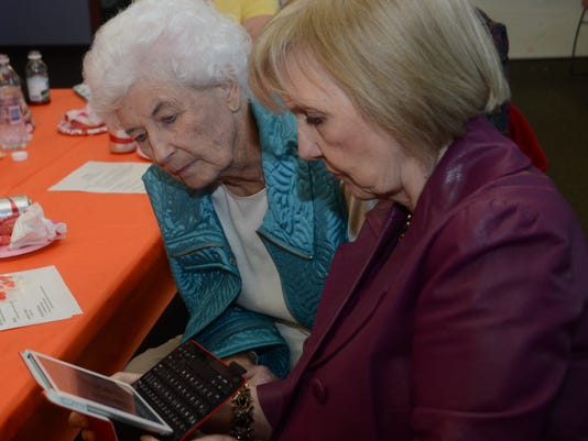 ANI Female educators meeting Gamma Kappa Delta members Doris Calcote (left) and Carolyn Pecanty look over pictures of ailments that Dr. Agnes Solon, a rheumatologist, discussed in her presentation. Solon was the guest speaker for the local chapter of Gamma