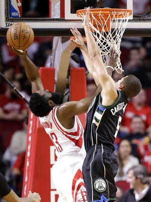 Houston Rockets' James Harden (13) goes up to shoot as Milwaukee Bucks' Michael Carter-Williams (5) defends during the first half of an NBA basketball game Friday in Houston. The Rockets won 102-98.