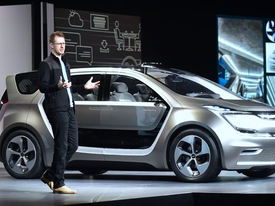 Exterior designer Matt Dunford speaks beside the unveiled Fiat Chrysler Portal Concept car during the Fiat Chrysler press conference at the 2017 Consumer Electronics Show  in Las Vegas on January 3, 2017.