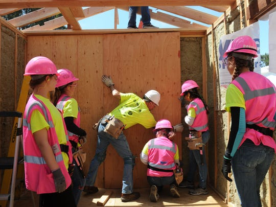 Volunteer Harv Humphrey, center, shows girls attending a construction camp how to screw a piece of wood onto the frame of the tiny house they are building.