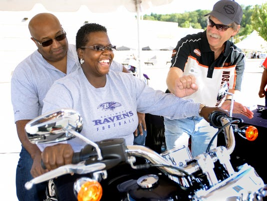 Marcia Shepperson and her husband Eric of York City get a lesson on motorcycle shifting from Harley-Davidson senior quality engineer Gary Swenson during the plant's open house Thursday, Sept. 24, 2015. The Jumpstart Experience gives first-time drivers a chance to spin the wheels on a stationary motorcycle. The open house, featuring demo rides on 2016 models, live music, food vendors and factory tours, continues Friday and Saturday from 9 a.m. to 4 p.m. Bill Kalina - bkalina@yorkdispatch.com