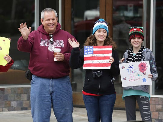 Vickie DeVenney, Kevin Morris, Whitney Morris and Abigail Thomasson, left to right,  wave. Thousands attended and participated in the Veterans Day Parade in Springfield, MO on Sat. Nov. 5, 2016.