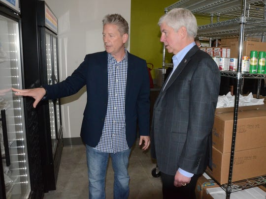 Mike McFarlen, who proposed the idea of The Fire Hub, shows Gov. Rich Snyder the food pantry.