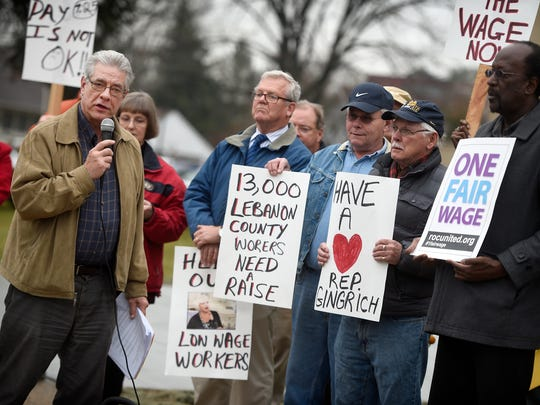 John Dodds introduces speakers during a protest at the Lebanon Municipal building Tuesday, Dec 22. The group is requesting that Rep. Mauree Gingrich introduce a bill to raise the minimum wage to $10.10 an hour.