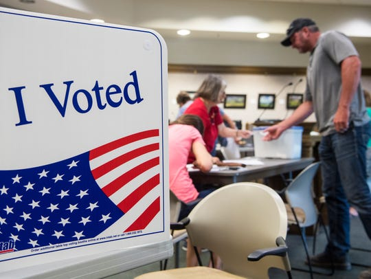 Poll workers help voters prepare ballots or change