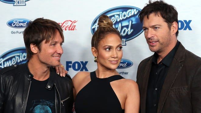 """Judges Keith Urban, left, Jennifer Lopez and Harry Connick Jr. huddle up at the """"American Idol"""" finalists celebration on Feb. 20 in West Hollywood."""