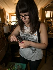 Dani Ausen, 32, repairs a necklace during the seventh